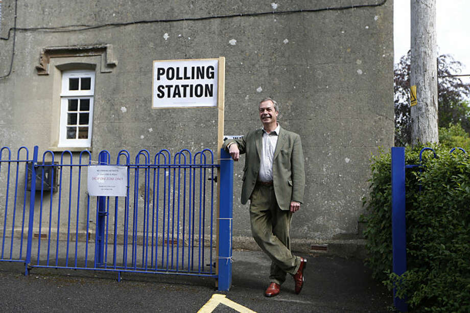 Nigel Farage, leader of Britain's United Kingdom Independence Party (UKIP) poses as he leaves after casting his vote for the European Parliament at a polling station in Cudham, England, Thursday, May 22, 2014. Farage's party could be on track to win the biggest share of British votes in elections for the European Parliament, a parliament Farage wants to abolish, along with the entire 28-nation EU bloc. (AP Photo/Sang Tan)