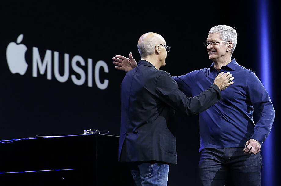 """Apple CEO Tim Cook, right, hugs Beats by Dre co-founder and Apple employee Jimmy Iovine at the Apple Worldwide Developers Conference in San Francisco, Monday, June 8, 2015. The maker of iPods and iPhones announced Apple Music, an app that combines a 24-hour, seven-day live radio station called """"Beats 1"""" with an on-demand music streaming service. (AP Photo/Jeff Chiu)"""