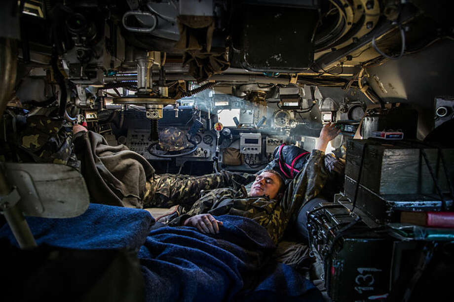 A Ukrainian government soldier rests inside an armored personnel carrier at a checkpoint near Slovyansk, Ukraine, Wednesday, May 21, 2014. The government has over the past week had its hand in the east strengthened by a sequence of strongly worded statements by metals tycoon Rinat Akhmetov, who owns major industrial assets in Donetsk region. (AP Photo/Petr Shelomovskiy)
