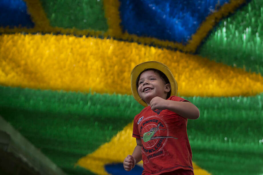 A boy plays on a street decorated for the upcoming World Cup in Manaus, Brazil, Wednesday, May 21, 2014. Manaus is one of the host cities for the 2014 World Cup in Brazil. (AP Photo/Felipe Dana)