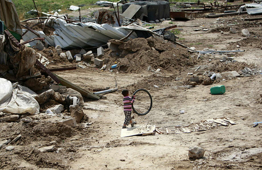 A Palestinian Bedouin child plays with a bicycle tire in the remains of his family's makeshift homes which were destroyed by the Israeli army near the West Bank city of Jericho in the Jordan valley, Wednesday, May 21, 2014. Palestinian security sources said the Israeli army destroyed more than 30 tents and sheds which the army said were illegally built close to the Jewish settlement of Meswah. (AP Photo/Mohammed Ballas)