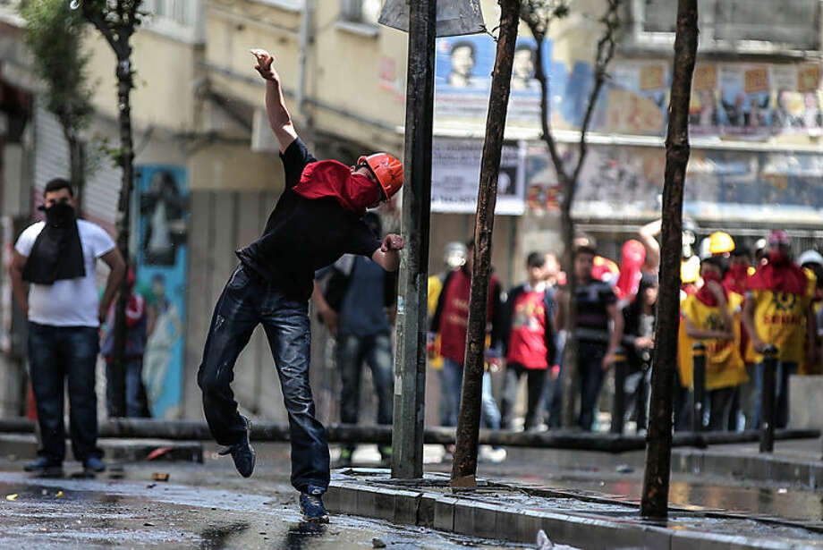 A masked man throws a stone as riot police use water cannons and teargas to disperse people who were protesting the Soma mine disaster that killed 301 miners, in Istanbul, Turkey, Thursday, March 22, 2014. A protester was seriously injured during clashes. (AP Photo/Emrah Gurel)