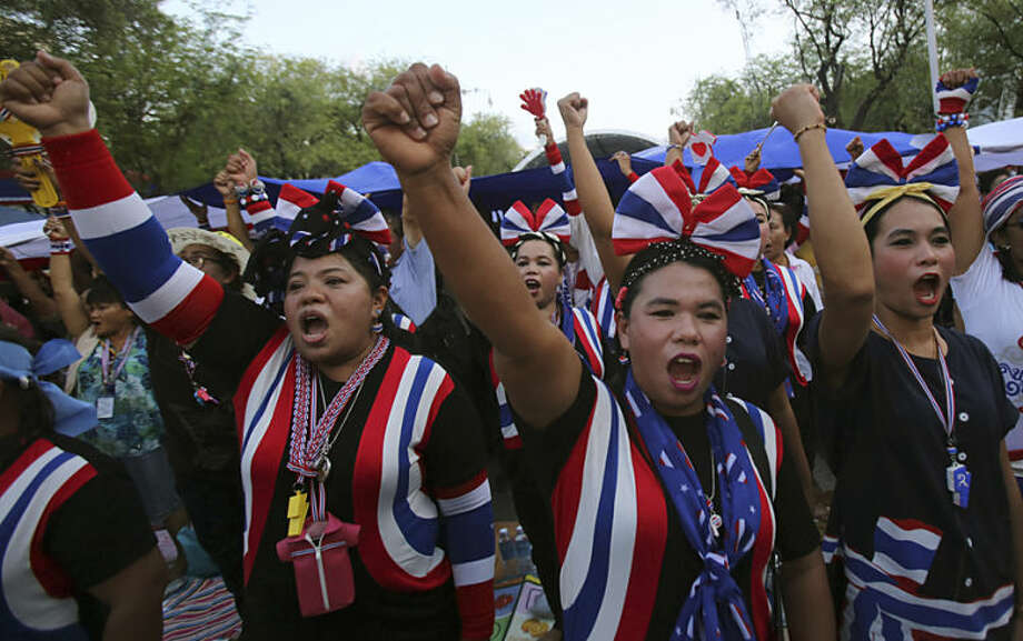 Anti-government protesters raise fists as they sing and listen to the national anthem during a gathering Thursday, May 22, 2014 in Bangkok, Thailand. Thailand's army chief announced a military takeover of the government Thursday, saying the coup was necessary to restore stability and order after six months of political deadlock and turmoil. (AP Photo/Sakchai Lalit)