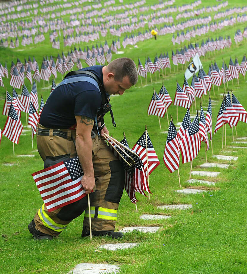Pittsburgh firefighter Brad Bennett plants flags on the graves of veterans in Allegheny Cemetery, May, 21, 2014, for the upcoming Memorial Day holiday. Bennett served two tours of duty in the U.S. Army's 28th Division in Iraq, 2005-06 and 2007-08. (AP Photo/Pittsburgh Post-Gazette, Larry Roberts)