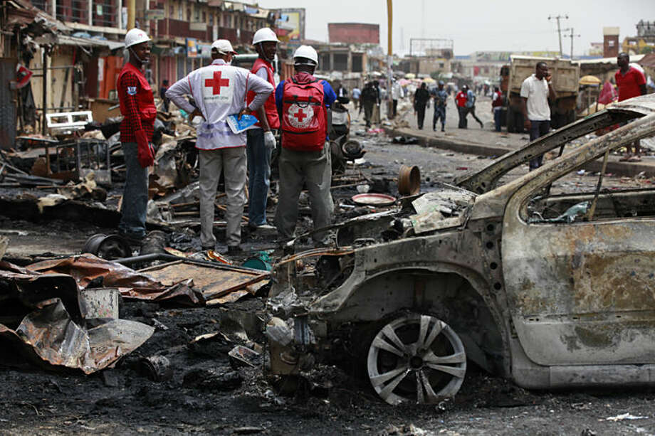 Red Cross personnel search for remains at the site of one of Tuesday's car bomb in Jos, Nigeria, Wednesday, May 21, 2014. Two car bombs exploded at a bustling bus terminal and market the central Nigeria city, killing at least 118 people, wounding dozens and leaving bloodied bodies amid the flaming debris. (AP Photo/Sunday Alamba)