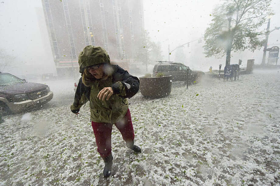 A pedestrian runs for safety as a hail storm hits downtown Colorado Springs, Colo., Wednesday, May 21, 2014. (AP Photo/The Gazette, Christian Murdock) MAGAZINES OUT.