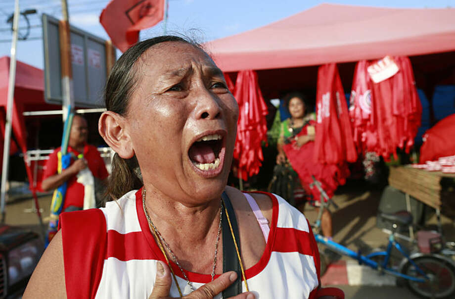 A pro-government demonstrator shouts as she leaves a demonstration site after soldiers staged the coup Thursday, May 22, 2014 on the outskirts of Bangkok, Thailand. Thailand's new military junta has announced that it has suspended the country's constitution. A military statement broadcast on national television Thursday confirmed the nation's caretaker government is no longer in power but said the Senate will remain in place. (AP Photo/Wason Wanichakorn)