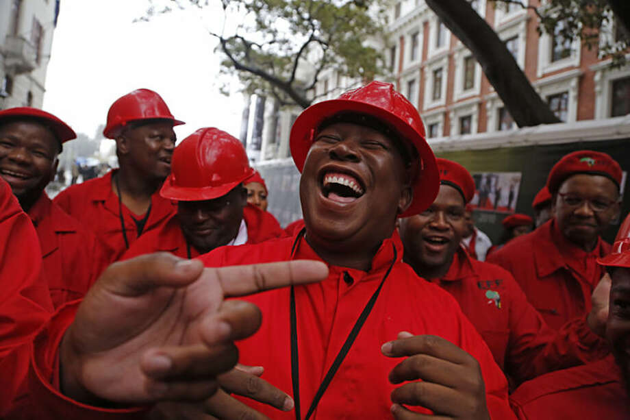 Julius Malema, center, leader of the Economic Freedom Fighters (EFF), arrives at Parliament wearing a hard hat and overall to show solidarity with coal mine workers, for the first sitting of the National Assembly after elections held in South Africa in Cape Town, South Africa, Wednesday, May 21, 2014. South Africa held its first sitting of Parliament on Wednesday, after recent elections, to swear in new members of parliament and to formally elect President Jacob Zuma as head of state. (AP Photo/Schalk van Zuydam)