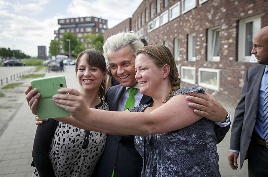 Geert Wilders, leader of the Dutch Party for Freedom, poses for a selfie with supporters as his bodyguard stand watch after casting his vote at a polling station in a school in The Hague, Netherlands, Thursday, May 22, 2014. Prominent Euroskeptic Wilders said he hopes for a higher-than-usual turnout in the Netherlands. From May 22-25, hundreds of millions of people from the European Union's 28 member countries will vote for members of the European Parliament, one of the EU's two legislative bodies. (AP Photo/Phil Nijhuis)