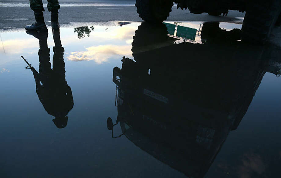 An armed Thai soldier is reflected in a puddle as he guards a road near a pro-government demonstration site on the outskirts of Bangkok, Thailand Wednesday, May 21, 2014. Thailand's army chief Gen. Prayuth Chan-Ocha assumed the role of mediator Wednesday by summoning the country's key political rivals for face-to-face talks one day after imposing martial law. The meeting ended without any resolution, however, underscoring the profound challenge the army faces in trying to end the country's crisis. (AP Photo/Wason Wanichakorn)