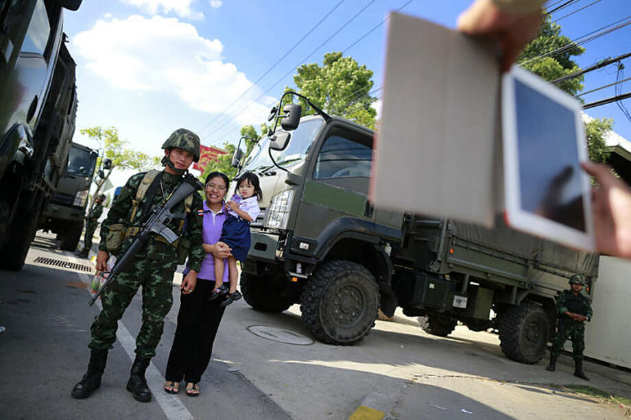A Thai mother and daughter have their photograph taken with a soldier guarding the area near a pro-government demonstration site on the outskirts of Bangkok, Thailand Wednesday, May 21, 2014. Thailand's army chief Gen. Prayuth Chan-Ocha assumed the role of mediator Wednesday by summoning the country's key political rivals for face-to-face talks one day after imposing martial law. The meeting ended without any resolution, however, underscoring the profound challenge the army faces in trying to end the country's crisis. (AP Photo/Wason Wanichakorn)