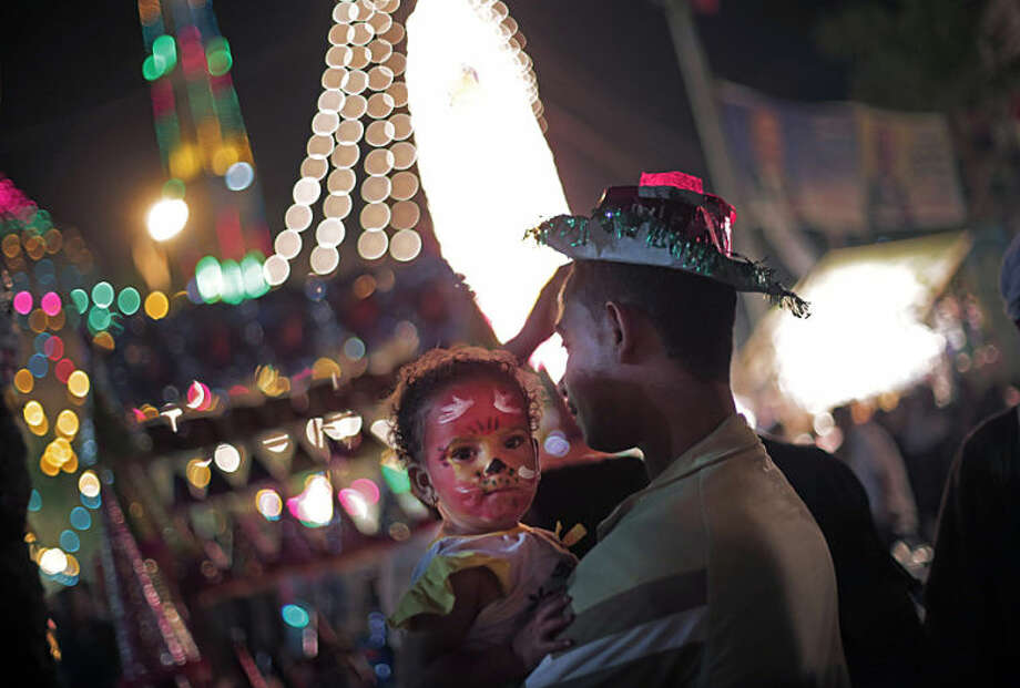 In this photo taken Tuesday, May 20, 2014, an Egyptian man holds his daughter as they celebrate Moulid outside the Sayyeda Zeinab shrine, in Cairo, Egypt. Every year, Egyptians celebrate Moulid, which commemorates of the birth of Muslim Prophet Mohammed's granddaughter, Zeinab, by performing ritual dances, prayers and having fun with their families.(AP Photo/Khalil Hamra)