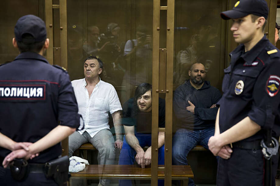 Background from left, Lom-Ali Gaitukayev, Ibragim Makhmudov, center, and Sergey Hadjikurbanov, accused of the murder of journalist Anna Politkovskaya, await the judge's verdict in a glass cage, at the Moscow City Court, Russia, Wednesday, May 21, 2014. A Moscow court has convicted five men of involvement in the murder of journalist Anna Politkovskaya, three of whom were acquitted in a previous trial. Tuesday's jury verdict found that Rustam Makhmudov was the gunman who shot Politkovskaya in the elevator of her Moscow apartment building in 2006 and that four others — his two brothers, their uncle and a former policeman — were accomplices. (AP Photo/Pavel Golovkin)