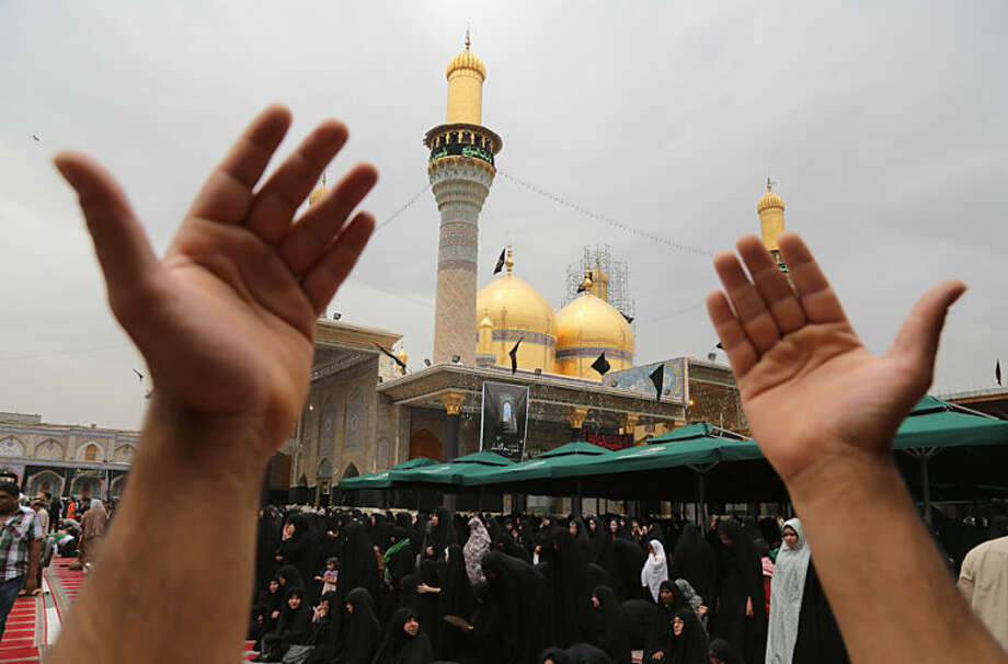 Shiite pilgrims pray at the Imam Moussa al-Kadhim shrine during the preparations for the annual commemoration of the saint's death in the Shiite district of Kazimiyah in Baghdad, Iraq, Thursday, May 22, 2014. Shiite pilgrims are expected to converge on the shrine in northern Baghdad during their annual march to commemorate the eighth-century death of Imam Moussa al-Kadhim, a key Shiite saint. (AP Photo/Karim Kadim)