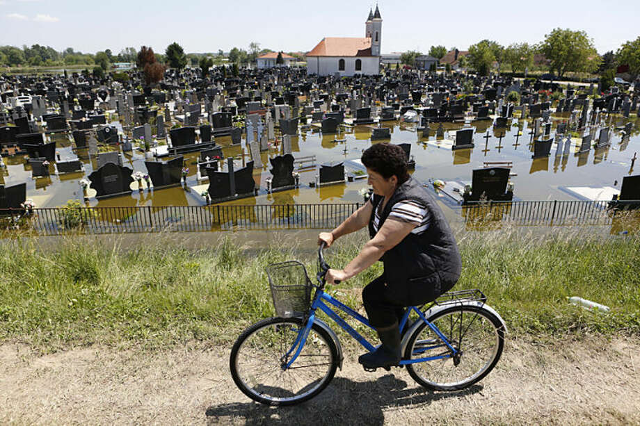 A Bosnian woman cycles past a flooded cemetery in the village of Domaljevac near the Bosnian town of Orasje along river Sava, 200 kms north of Bosnian capital of Sarajevo, on Wednesday, May 21, 2014. Floodwaters receded Wednesday in Bosnia and Serbia, just enough to reveal the next shock: recovery from the historic flood will probably cost billions of euros that neither of the countries has. (AP Photo/Amel Emric)
