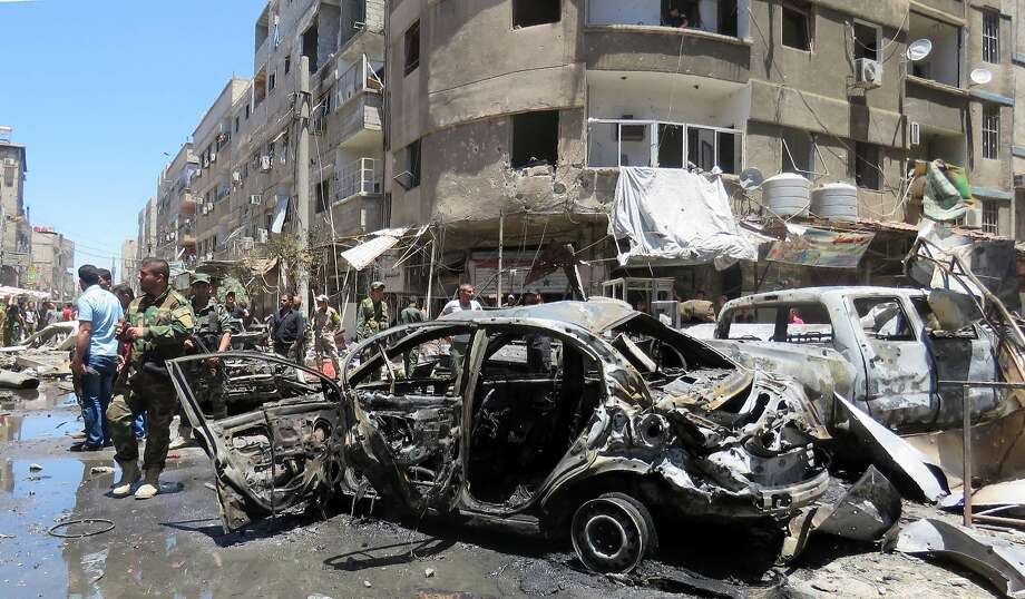 TOPSHOT - Syrians gather at the scene of a double bombing attack on June 11, 2016 outside the Sayyida Zeinab shrine, which is revered by Shiites around the world, some ten kilometres south of the centre of Damascus, in the latest in repeated deadly strikes on the revered site. The official SANA news agency said a suicide bomber and a car bomb struck at the entrance to the shrine. / AFP PHOTO / STRINGERSTRINGER/AFP/Getty Images Photo: STRINGER, AFP/Getty Images