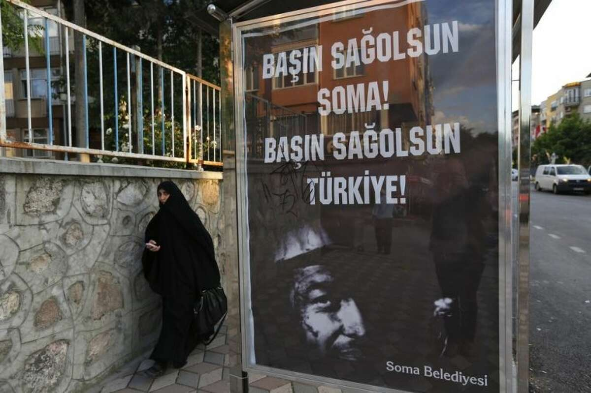 A woman walks past a bus stop with a poster offering condolences in Turkish to Soma and Turkey, in Soma, western Turkey, where the mine accident occurred, Saturday, May 17, 2014. An explosion and fire at a coal mine in Soma, some 250 kilometers (155 miles) south of Istanbul, killed hundreds of workers in one of the worst mining disasters in Turkish history. (AP Photo/Lefteris Pitarakis)
