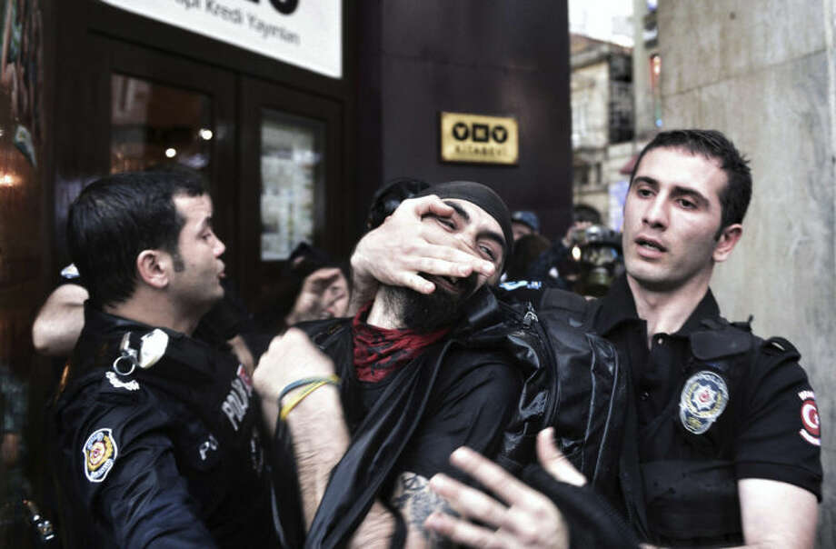 Riot police detain a protester as they use water cannons and teargas to disperse people who were protesting the Soma mine accident that killed 301 miners, in Istanbul, Turkey, Saturday, May 17, 2014. Turkey's Energy Minister Taner Yildiz said Saturday that crews had found more bodies overnight, raising the death toll to 301. An explosion and fire at a coal mine in Soma, some 250 kilometers (155 miles) south of Istanbul, killed hundreds of workers in one of the worst mining disasters in Turkish history. (AP Photo