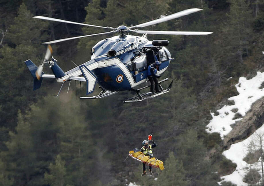 FILE - In this Thursday March 26, 2015 file photo a rescue worker is lifted into a helicopter at the crash site near near Seyne-les-Alpes, France. Dozens of relatives of victims of the Germanwings crash in the French Alps are awaiting the return of remains of their loved ones, roughly 2-1/2 months after the disaster killed all 150 people on board. In the first repatriation yet, a total of 44 coffins were expected to be flown Tuesday from Marseille, France, to Duesseldorf, Germany. (AP Photo/Laurent Cipriani, File)