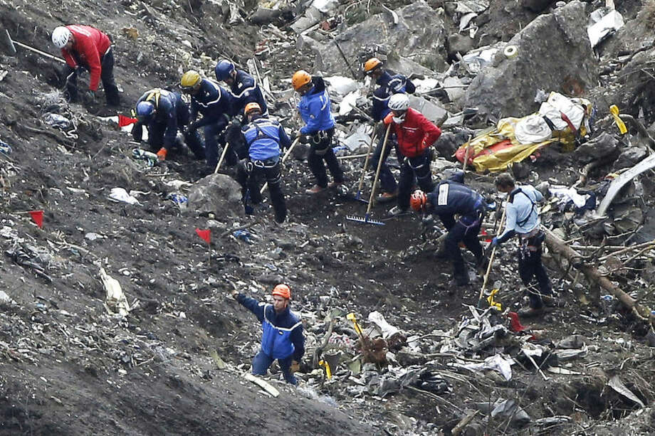 FILE - In this March 26, 2015 file photo, rescue workers work on debris of the Germanwings jet at the crash site near Seyne-les-Alpes, France. Dozens of relatives of victims of the Germanwings crash in the French Alps are awaiting the return of remains of their loved ones, roughly 2-1/2 months after the disaster killed all 150 people on board. In the first repatriation yet, a total of 44 coffins were expected to be flown Tuesday from Marseille, France, to Duesseldorf, Germany. (AP Photo/Laurent Cipriani, File)
