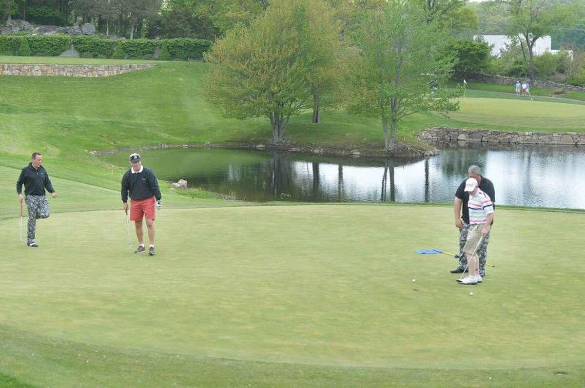 Hour Photo/Alex von Kleydorff Teddy Gallagher, watches as Dave Bayle puts with Ryan Grant and Richard Courville during All Saints Catholic School Golf Tournament at Silvermine Golf Club