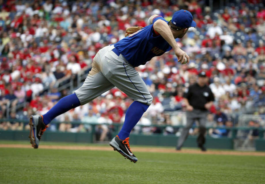 New York Mets third baseman David Wright prepares to throw to first base, but Washington Nationals' Anthony Rendon was safe, during the third inning of a baseball game at Nationals Park Sunday, May 18, 2014, in Washington. (AP Photo/Alex Brandon)