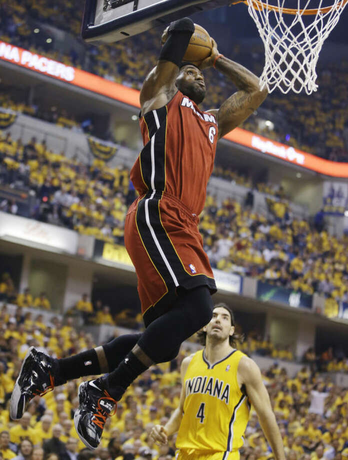 Miami Heat forward LeBron James (6) dunks as Indiana Pacers forward Luis Scola (4) looks on during the first half of Game 1 of the Eastern Conference finals NBA basketball playoff series Sunday, May 18, 2014, in Indianapolis. (AP Photo/Darron Cummings)