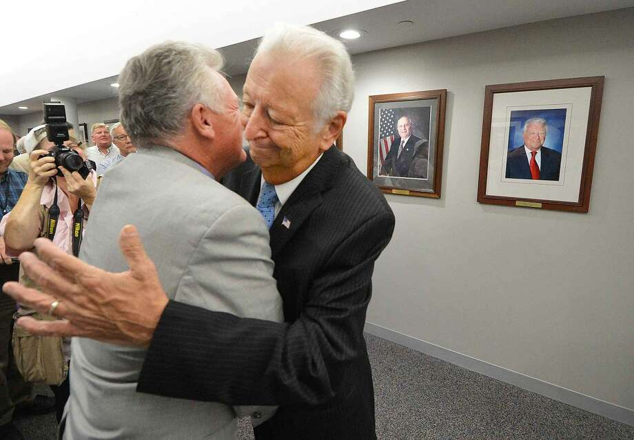 Hour Photo/Alex von Kleydorff Mayor Harry Rilling and former Mayor Richard Moccia hug after the former mayor's official portrait was unveiled in the Mayors Portrait Gallery at City Hall on Wednesday
