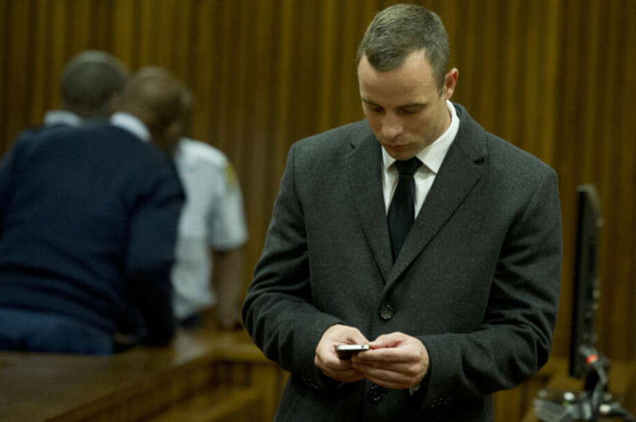 Oscar Pistorius checks his mobile phone in court in Pretoria, South Africa, Tuesday, May 20, 2014, after a ruling was read out by Judge Thokozile Masipa that he would undergo psychiatric evaluation. Pistorius is charged with the shooting death of his girlfriend Reeva Steenkamp on Valentine's Day in 2013. (AP Photo/Deean Vivier, Pool)