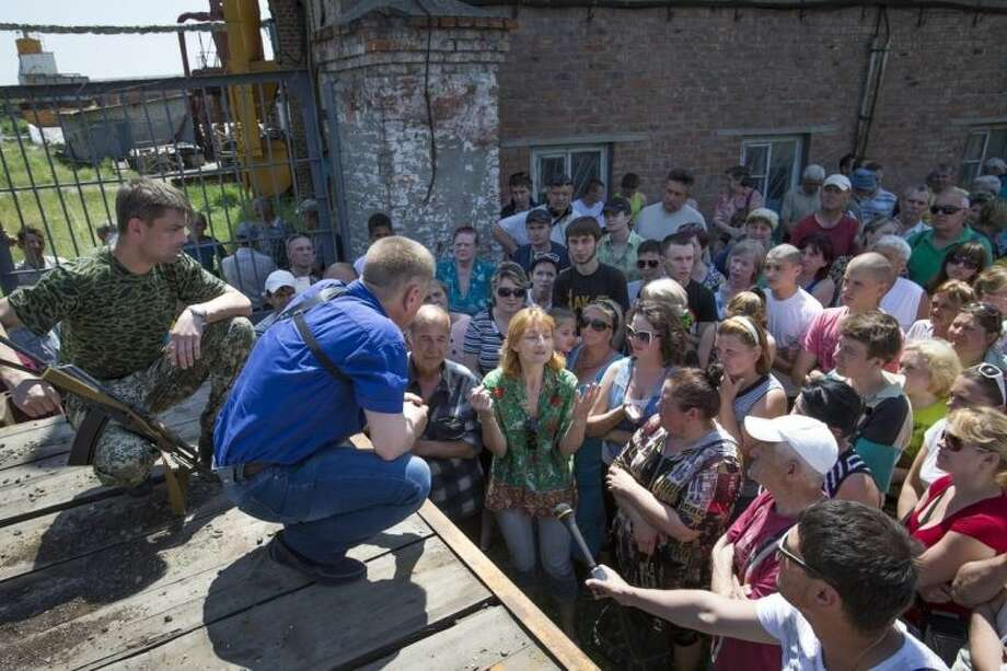 Vyacheslav Ponomarev, center, the self-proclaimed mayor of Slovyansk talks with local citizens whose homes were ruined in a shelling in Slovyansk, eastern Ukraine, Tuesday, May 20, 2014. On Tuesday, the rebels continued to exchange fire with government forces on the outskirts of the eastern city of Slovyansk, which has been the epicenter of clashes. Residents of Slovyansk sounded exasperated and angry with both the warring sides. (AP Photo/Alexander Zemlianichenko)