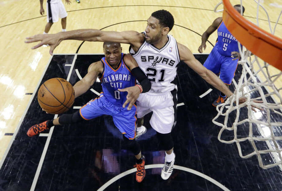 Oklahoma City Thunder's Russell Westbrook (0) is defended by San Antonio Spurs' Tim Duncan (21) as he drives to the basket during the first half of Game 1 of a Western Conference finals NBA basketball playoff series, Monday, May 19, 2014, in San Antonio. San Antonio won 122-105. (AP Photo/Eric Gay)