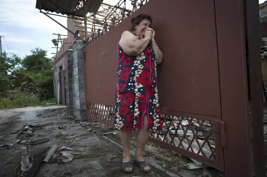 Yekaterina Len, 61, cries outside her ruined house following a shelling in Slovyansk, eastern Ukraine, Tuesday, May 20, 2014. Slovyansk has been the major fighting ground between pro-Russian insurgents and Ukrainian government troops in eastern Ukraine. (AP Photo/Alexander Zemlianichenko)