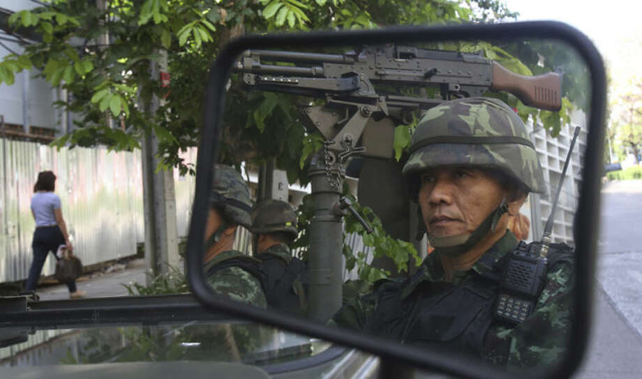 Thai soldiers are reflected in a mirror while guarding the Thai police headquarters Tuesday, May 20, 2014, in Bangkok, Thailand. Thailand's army declared martial law before dawn Tuesday in a surprise announcement it said was aimed at keeping the country stable after six months of sometimes violent political unrest. The military, however, denied a coup d'etat was underway. (AP Photo/Sakchai Lalit)
