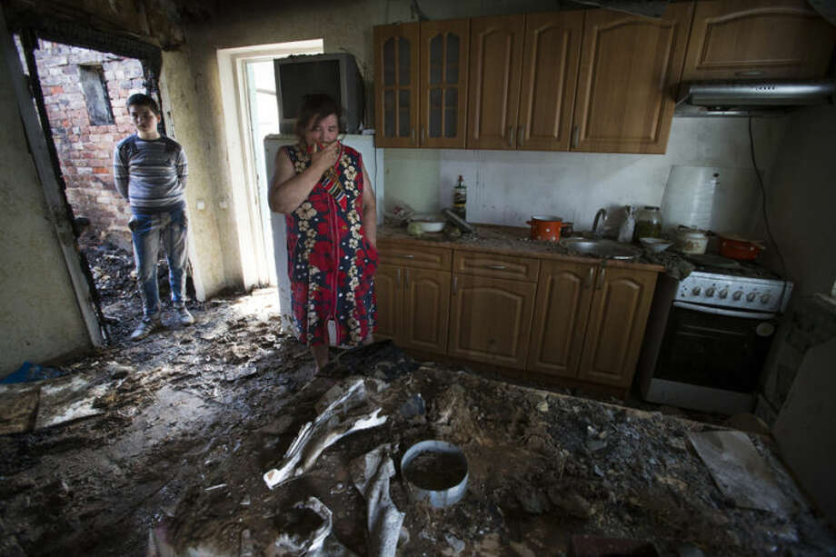 Yekaterina Len, 61, center, cries inside her ruined house following a shelling as her grandson stands behind her in Slovyansk, eastern Ukraine, Tuesday, May 20, 2014. Slovyansk has been the major fighting ground between pro-Russian insurgents and Ukrainian government troops in eastern Ukraine. (AP Photo/Alexander Zemlianichenko)