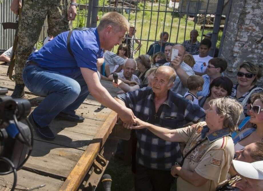 Vyacheslav Ponomarev, left, the self-proclaimed mayor of Slovyansk, shakes hands with a woman during his meeting with local citizens whose homes were ruined in a shelling in Slovyansk, eastern Ukraine, Tuesday, May 20, 2014. On Tuesday, the rebels continued to exchange fire with government forces on the outskirts of the eastern city of Slovyansk, which has been the epicenter of clashes. Residents of Slovyansk sounded exasperated and angry with both the warring sides. (AP Photo/Alexander Zemlianichenko)