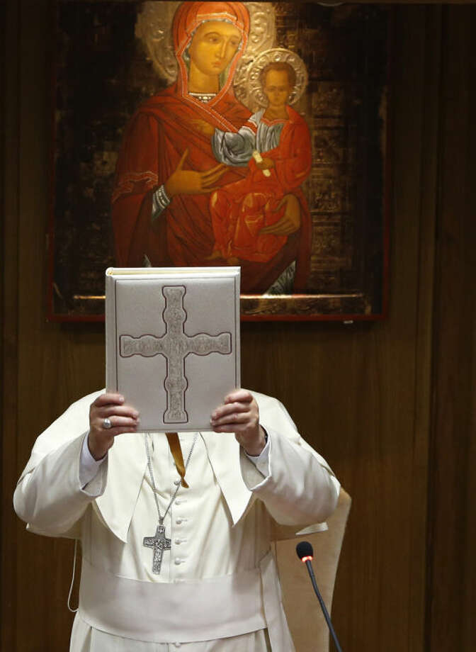 Pope Francis lifts the Gospel book during the opening session of the Italian Episcopal Conference's meeting at the Vatican, Monday, May 19, 2014. (AP Photo/Riccardo De Luca)