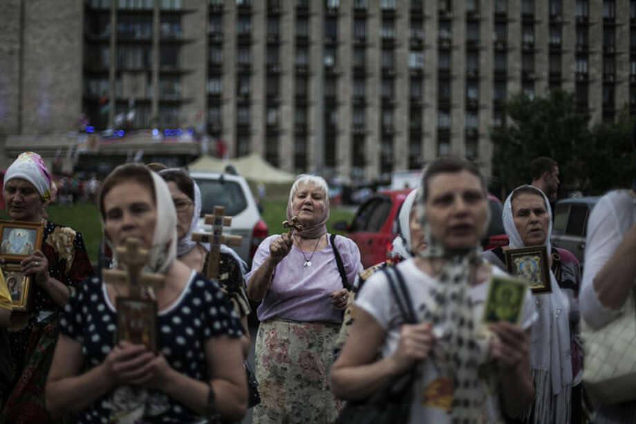 Pro-Russian woman pray while attending a public prayer for peace in front of the occupied administration building in Donetsk, eastern Ukraine, Monday, May 19, 2014. what could be a move to ease tensions with the West and avoid more sanctions, President Vladimir Putin ordered Russian troops deployed near Ukraine to return to their home bases Monday. (AP Photo/Manu Brabo)