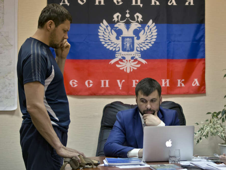 A body guard holds a pistol as insurgent leader Denis Pushilin, right, sits backdropped by the flag of the Donetsk Republic, in Donetsk, Ukraine, Monday, May 19, 2014. Ukraine will hold presidential elections on May 25. (AP Photo/Vadim Ghirda)