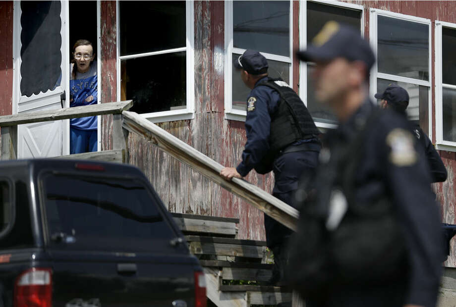 Law enforcement officers question a woman that lives near the prison in Dannemora, N.Y., as they searched houses near the maximum-security prison in northern New York where two killers escaped using power tools,Wednesday, June 10, 2015. State Police said the fifth day of searching will entail going from house to house in Dannemora, where David Sweat and Richard Matt cut their way out of the Clinton Correctional Facility. (AP Photo/Seth Wenig)