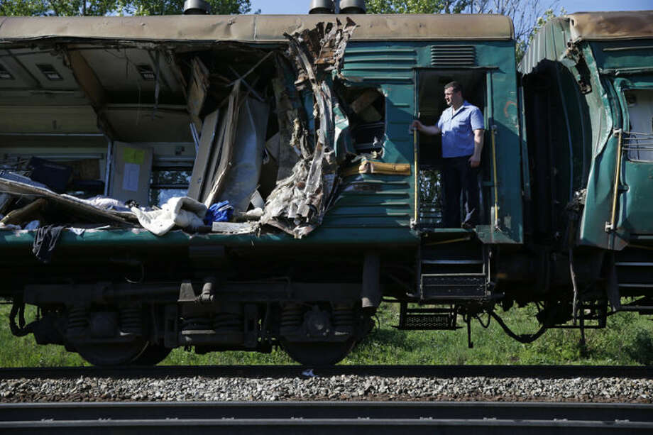 A train conductor stands at a door of a damaged railway car at the site of train collision near the city of Naro-Fominsk outside Moscow Tuesday May 20, 2014. The Interior Ministry said the accident happened when several cars of a cargo train derailed and hit a passenger train near Naro-Fominsk, a town 50 kilometers (30 miles) southwest of Moscow. (AP Photo/ Pavel Golovkin)