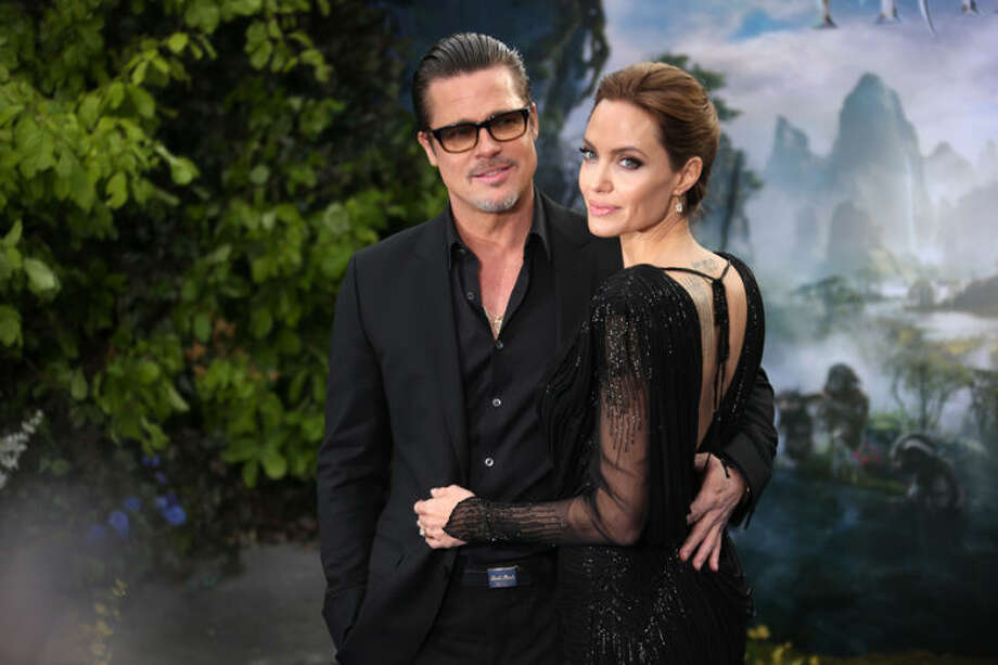"""In this Thursday, May 8, 2014 file photo, actors Brad Pitt and Angelina Jolie arrive for the """"Maleficent"""" exhibit in Kensington Gardens, London. The exhibit showcases some of the costumes and props from the film """"Maleficent,"""" before they go on display to the public at the O2 in London. The film releases in theaters in the U.S. on May 30, 2014. (Joel Ryan/Invision/AP, file)"""