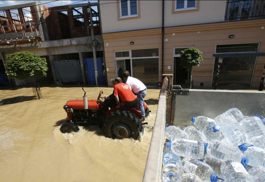 People ride on tractor in a flooded street in Obrenovac, some 30 kilometers (18 miles) southwest of Belgrade, Serbia, Monday, May 19, 2014. Belgrade braced for a river surge Monday that threatened to inundate Serbia's main power plant and cause major power cuts in the crisis-stricken country as the Balkans struggle with the consequences of the worst flooding in southeastern Europe in more than a century. At least 35 people have died in Serbia and Bosnia in the five days of flooding caused by unprecedented torrential rain, laying waste to entire towns and villages and sending tens of thousands of people out of their homes, authorities said. (AP Photo/Darko Vojinovic)