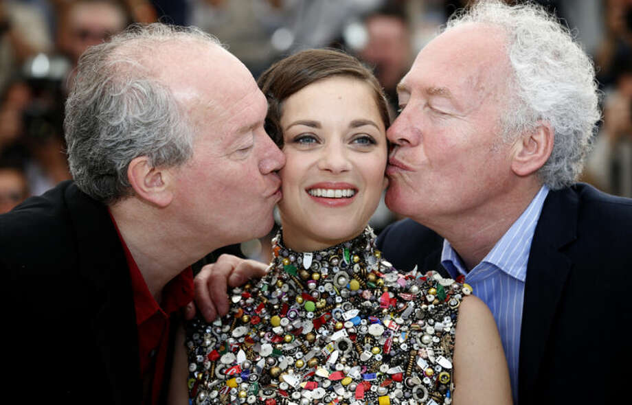 Director Jean-Pierre Dardenne, right, and director Luc Dardenne, left, kiss actress Marion Cotillard as they pose for photographers during a photo call for Two Days, One Night (Deux jours, une nuit) at the 67th international film festival, Cannes, southern France, Tuesday, May 20, 2014. (AP Photo/Alastair Grant)