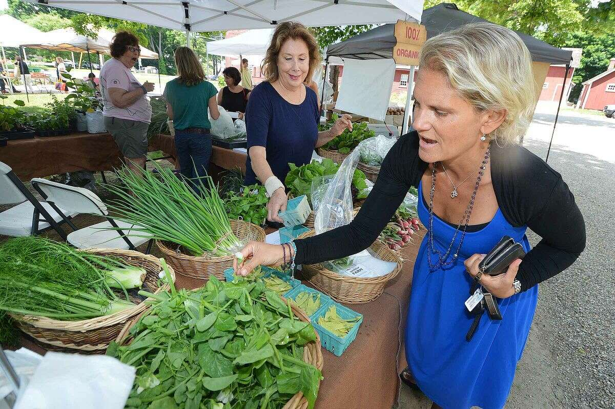 Hour Photo/Alex von Kleydorff Victoria Shaw grabs some fresh pea tendrils, which are the young leaves and shoots from the snow pea plant, with help from Marie Florine while stoping by the Ambler Farm stand at the Wilton Farmers Market on Wednesday, its opening day.