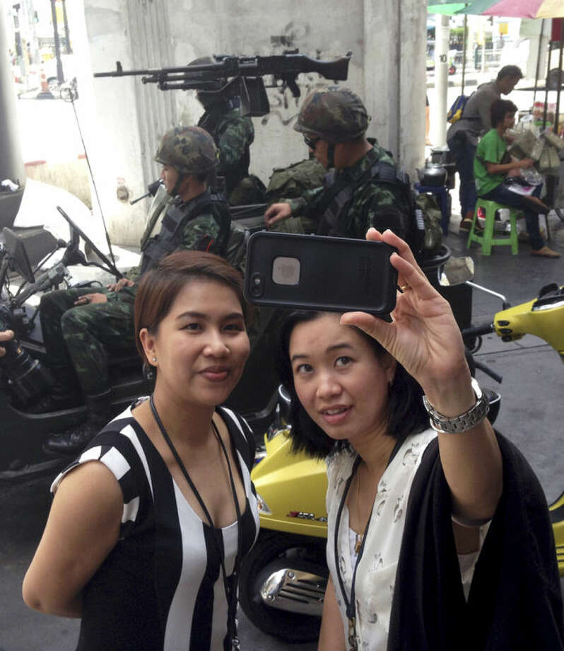 Residents stop to take a photograph of themselves at a military checkpoint in central Bangkok, Tuesday, May 20, 2014. Thailand's army declared martial law in a surprise announcement before dawn Tuesday that it said was aimed at keeping the country stable after six months of sometimes violent political unrest. The military, however, denied a coup d'etat was underway. (AP Photo/Kiko Rosario)