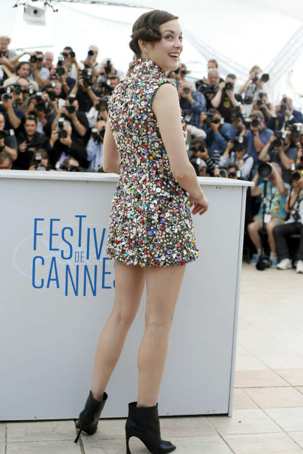 Actress Marion Cotillard poses for a photographers during a photo call for Two Days, One Night (Deux jours, une nuit) at the 67th international film festival, Cannes, southern France, Tuesday, May 20, 2014. (AP Photo/Alastair Grant)