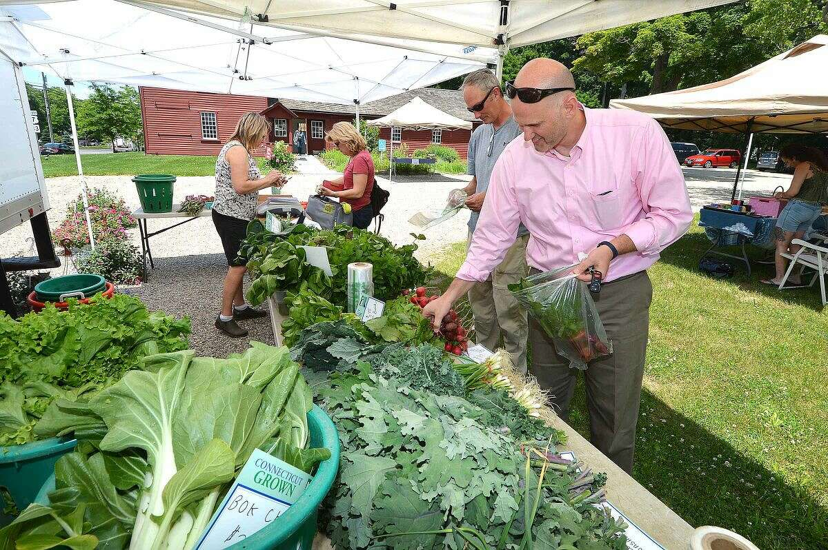 Hour Photo/Alex von Kleydorff Chris D'Amato buys some fresh beets from the Gazy Bros farm stand during Wilton Farmers Market