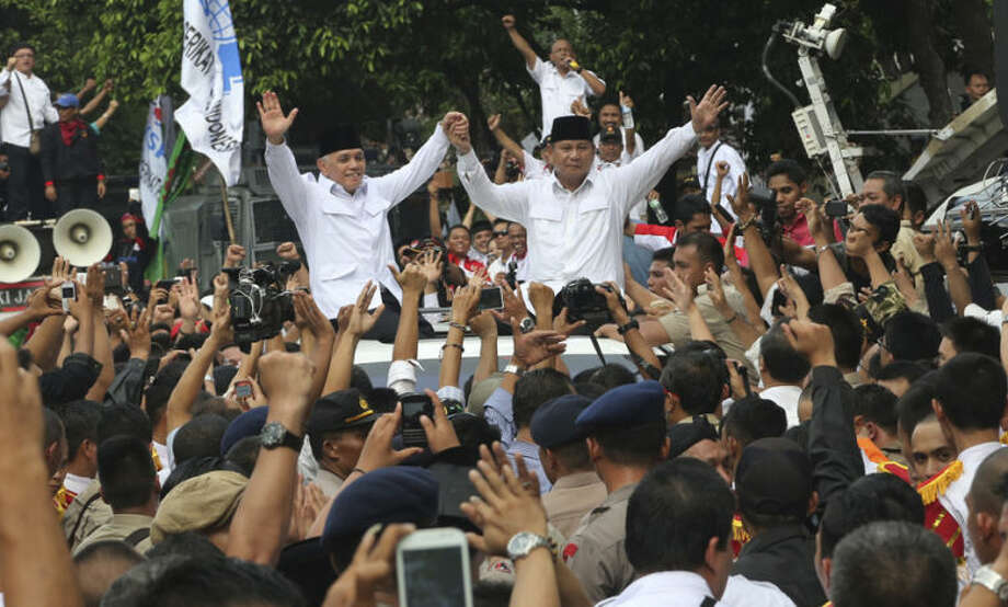 Indonesian presidential candidate Prabowo Subianto, right, and his running mate Hatta Rajasa, left, wave to their supporters after registering their candidacy at the General Election Commission's office in Jakarta, Indonesia, Tuesday, May 20, 2014. Indonesia is scheduled to hold presidential elections in July. (AP Photo/Tatan Syuflana)