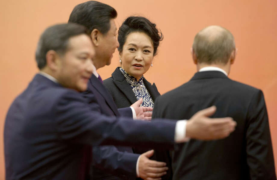 Chinese first lady Peng Liyuan, center, looks at Russian President Vladimir Putin, right, and Chinese President Xi Jinping, second left, as they arrive for a group photo for the fourth summit of the Conference on Interaction and Confidence Building Measures in Asia (CICA)in Shanghai, China, Tuesday, May 20, 2014. Putin met Tuesday with China's president in a diplomatic boost for the isolated Russian leader but the two sides had yet to agree on a widely anticipated multibillion-dollar natural gas sale. (AP Photo/Ng Han Guan, Pool)