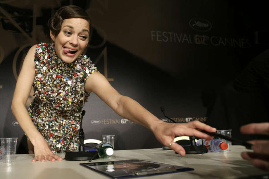 Actress Marion Cotillard signs autographs following a press conference for Two Days, One Night (Deux jours, une nuit) at the 67th international film festival, Cannes, southern France, Tuesday, May 20, 2014. (AP Photo/Thibault Camus)